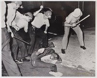 Black and white press print of four white policemen beating an African American man with clubs, who covers his head while lying on the pavement.