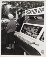 Black and white press print of a suited white male (George Wallace) speaking into a microphone to a small crowd. A campaign car and an older white woman (not facing the camera) are in the near foreground.