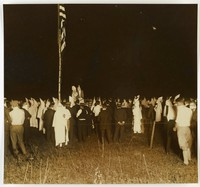 Black and white press print of a large crowd congregated in what appears to be a field at nighttime. Some wear KKK hoods and outfits, others are dressed in suits. An American flag hangs from a flag pole on the left side. Two Klansmen seem to be on a raised platform in the center of the crowd (not facing the camera).