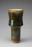 Heavy thistle-shaped vase that tapers inward to a cylindrical base. The vase's exterior is a mixture of multiple colors throughout - light and dark brown, dark green, black, and the color of the unglazed stoneware. The dark glaze begins near the middle of  the vase, continuing downward to the bottom of the thistle form and pooling in drips and continuing towards the bottom of the vase. The vase's exterior features thin lines impressed horizontally into the form. The lines are irregularly spaced throughout the vase, occuring mostly at the top of the vase, on the bottom half of the thistle form, and the bottom of the cylindrical base. The vase's lip is mostly dark brown and unglazed stoneware. The vase's interior is unglazed stoneware with thin, raised lines circling the form that correspond in placement with the impressed lines on the exterior.