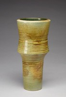 Heavy thistle-shaped vase that tapers inward to a cylindrical base. The vase's exterior is smooth in texture and is green, varying in tone from gray-green to olive green and khaki. The exterior is flecked with brown specks. The exterior has impressed, horizontal lines around the vase's form, irregular in size but fairly consistent in placement along the vase. The vase's interior is glazed dark green and has thin, raised horizontal lines corresponding in placement to the exterior's horizontal lines.