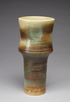 Heavy thistle-shaped vase that tapers inward to a cylindrical base. The vase's exterior is a mix of dark and light brown, teal, green, light blue, black, and off-white stoneware. The vase's glaze is irregularly applied, creating areas of buildup, most notably the blue spots near the top of the vase and the dark blue/black area around the top of the cylindrical base of the vase. There are some uniform glaze blisters below one of the blue spots of glaze near the top of the vase and along the edge of the vase to the left, almost appearing like holes cut into the glaze. The vase's exterior is covered in thin, horizontal impressed lines that circle the form, creating ridges along the exterior that catch the glaze. The vase's interior is unglazed, off-white stoneware with raised, thins lines corresponding to the exterior's impressed lines.