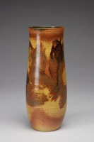 Vase with cylindrical, slightly waisted form. The exterior is decorated with some indented bands that vary in width wrapped around the vase, mostly on the bottom half or near the lip of the vase. It has a mustard/tan body that is decorated with painterly brushes of brown and black, some with a veinlike design in them. Near the base and lip are bands of brown with a rougher texture. The bottom of the base is not glazed. The interior is decorated with a black and green irregular glaze.