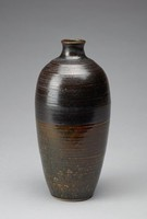 A vase with a bottle-like form. It is heavy and primarily black in color. The upper part o fthe vase has interspersed thin, red, and horizontal lines. The lower half of the vase features a dripping glaze on top of a mix of black bands, dark red, moss green, and white specks.There are some imperfections and air bubbled along the body of the vase. The vase's exterior lip is ringed in dark red and the interior of the vase's lip is ringed with dark green. The vase's interior is unglazed.