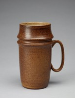 Mug with a rounded cylindrical form that flares out at two points and tapers towards the base. The mug's exterior is speckled dark brown stoneware. Two areas near the handle appear almost smeared, like they were disturbed before the glaze was dry. There is also a blank area with few dark brown spots near the base o fthe mug. The exterior of the mug has thin horizontal, imprinted lines uniformly circling the form. The lip and interior are off-white toneware with dark-brown specks.