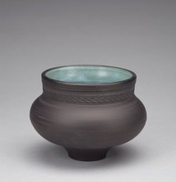 Round, bulbous vase of black basalt on a very narrow, stout foot, with a long neck that has impressed geometric motifs around created by the roulette wheel, and wide opening, the interior covered with a slightly transparent light blue glaze.