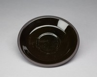 Slightly convex dish with impressions for a cup. The dish's exterior is smooth black basalt. The interior is glazed black and the dish's lip is unglazed. There are two concentric circles impressed into the dish's interior.