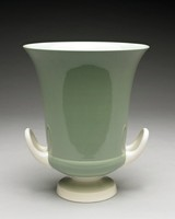 A two-handled vase, Keith Murray shape 4225, in two-tone slipware. Celadon green slip on body with cream handles and foot. The handles are upturned and looped, and placed at the lower body near the foot. The body flares at the mouth and tapers toward the foot.