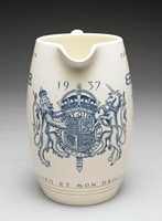 Keith Murray designed creamware pitcher, Murray shape 4193, with printed commemorative imagery in blue ink. The pitcher is barrel shaped with a handle and spout. Three engine-turned bands encircle the foot. Imagery on the body commemorates the coronation of King Edward VIII, and includes a large image, below the spout, of the royal coat of arms held by a monkey on the left and a unicorn on the right. The year 1937 appears above the image. Below the image reads: DIEU ET MON DROIT. To the left of the monkey appears text, reading top to bottom: Coronation; ER; DEI : GRA; BRITT; OMN : REX. On the right, text: EDWARD VIII; ER; FID : DEF; IND : IMP.