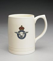 Large cylindrical creamware mug with pointed loop handle, shape number 3810 by Keith Murray, covered with matt moonstone glaze and decorated on one side with the British Air Force insignia printed in multi-color (black, blue, red, gold).