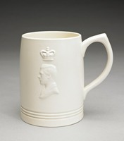 Large cylindrical creamware mug with pointed loop handle, shape number 3810 by Keith Murray, covered with a creamy, matte white Moonstone glaze and decorated on one side with the bas relief portrait of Edward VIII (reigned January 20-December 11,1936) facing left below a crown.