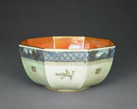 Octagonal butterfly lustre bowl with orange interior and mother-of-pearl exterior. The bowl has a solid golden trim on the upper and bottom rim. A wide golden geometric pattern (3.5cm) in the upper third is placed over blue glaze, intersected with four framed medallions showing Asian-inspired architecture and vegetation. The scene of the medallions on opposite sides are the same. A pattern of continuous husks of wheats is set underneath. The body of the bowl is decorated with four golden flying birds carrying a seated person on their back. Two of the birds have their necks retracted, the other two have an outstretched neck. The birds are alternated with a depiction of a rabbit on the remaining four plains of the bowl.  A golden, endless Greek-key pattern decorates the bottom rim. The vibrant, mottled orange interior glaze is decorated with a wide golden trellis band (3cm) with blue bells hanging underneath. Three large, golden butterflies in different positons (open/closed wings) are alternating with three small, golden butterflies with open wings. Part of the butterflies are highlighted with red, green and blue glaze. The bottom of the bowl is decorated with a large golden rosette with red, green and blue glaze.