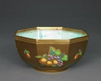 Octagonal lustre bowl with bronze exterior and mottled pearlized blue interior, fruit designs.Four of the eight fields on the outside of the bowl are decorated with larger fruit arrangements.a) grapes (purple glaze), a pear (orange/yellow glaze), leaves (green glaze), gilding used to outline the design.b) grapes (purple glaze), two peaches (orange/yellow glaze), and leaves (green glaze), gilding used to outline the design. c) grapes (purple glaze), an apricot (orange/yellow glaze), and leaves (green glaze), gilding used to outline the design.  d) grapes (purple glaze), three mirabelles (orange/yellow glaze), and leaves (green glaze), gilding used to outline the design.  These designs are alternated with individual fruit designs.a) a strawberry (orange/yellow/red glaze), and leaves (green glaze), gilding used to outline the design.b) a plum (purple glaze), and leaves (green glaze), gilding used to outline the design.c) a blackberry (purple glaze), and leaves (green glaze), gilding used to outline the design.d) an apricot (orange/yellow/red glaze), and leaves (green glaze), gilding used to outline the design.A rope-like pattern decorates the upper rim of the outside of the bowl.The inside has a mother-of-pearl glaze with a geometric, gilded pattern along the upper rim of the bowl with a red glaze. In the inside there are six individual fruits equally distributed throughout the bowl, halfway up the side. a) a strawberry (orange/yellow/red glaze), and leaves (green glaze), gilding used to outline the design.b) a plum (purple glaze), and leaves (green glaze), gilding used to outline the design.c) a raspberry (orange/yellow/red glaze), and leaves (green glaze), gilding used to outline the design.d) a plum (purple glaze), and leaves (green glaze), gilding used to outline the design.e) an apricot (orange/yellow/red glaze), and leaves (green glaze), gilding used to outline the design.f) a plum (purple glaze), and leaves (green glaze), gilding used to outline the design.The b