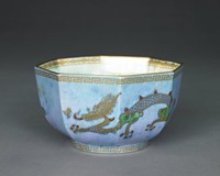 Octagonal dragon lustre bowl with lavender/blue exterior, and pale turquoise pearlized interior.The outside of the bowl is decorated with a golden, endless Greek key pattern along the upper and bottom rim.  A solid golden trim is at the top and bottom rim. Two outstretched three-legged, four-clawed golden dragons with scales and a curled tail stretching across three fields of the octagonal bowl, each. The dragons have outstretched tongues, bulging eyes, a mane and some spikes along their backs. The spikes, part of the face, tongue, tail and claws are highlighted with red glaze. The shoulders and hips of the dragons are highlighted with green glaze. The dragons have a cross on their upper jaw and a dragonfly hovers in front of them. The upper, inside, rim is decorated with a repeating oval and diamond pattern. Below are three outstretched, scaled, golden dragons, equally distributed. Different parts of the body are highlighted with purple, red and green glaze. The bottom of the bowl is decorated with golden geometric and floral pattern on purple, red and green glaze.