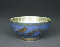 Dragon lustre bowl with blue exterior and mother-of-pearl interior.The outside of the bowl is decorated with a golden, endless Greek key pattern along the upper rim. A golden pierced band pattern is at the bottom rim of the bowl. A solid golden trim is at the top and bottom rim. Two outstretched three-legged, four-clawed golden dragons with scales and a curled tail stretching across one half of the bowl, each. The dragons have outstretched tongues, bulging eyes, a mane and some spikes along their backs. The spikes, part of the face, and claws are highlighted with red glaze. The dragons have a cross on their upper jaw and a dragonfly hovers in front of them. There is a golden, cloud-like motif with red glaze dividing the two dragons.The upper rim of the inside of the bowl is decorated with a golden arabesque pattern. At the bottom is a fierce, four-legged, curled dragon with a mane. His right front leg is grasping a part of his tail. Different parts of the dragon's body are highlighted with red, blue, orange, yellow and green glaze.