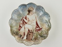 Round, shallow, pearlware dish with scalloped edges, the well and sides of the dish painted with the scene of a seated nude female looking to her left, she holds a pink cloak or drapery in both hands around her back and a white cloth is draped over her lap, in front of her is a large brown urn for carrying water, she sits in a landscape with leafy green water foliage and blue sky behind her.