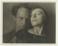 This black and white photograph shows a woman, eyes partially closed, leaning backward onto a man. The man is positioned to the left of the woman and stares directly at the camera.
