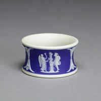 Napkin ring of white jasper with dark blue jasper dip and white relief decoration comprised of three small relief scenes divided by decorative elements, the scenes include the Bourbonnais Shepherd, Nike and a Warrior, and a group with a cage.