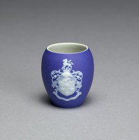 """Miniature commemorative spill vase of vase form of white jasper with dark blue jasper dip and white relief decoration, on one side the portrait bust of Josiah Wedgwood with the name JOSIAH WEDGWOOD and dates 1730-1795 in banners below, on the other the coat of arms of the Wedgwood baronetcy Gules four Mullets in Cross and a Canton Argent and on a Ducal Coronet a Lion passant Argent with the motto """"Obstantia Discindo"""" (I split asunder obstacles) in a banner below."""
