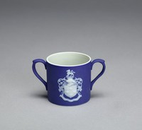 Miniature two-handled mug of white jasper with a dark blue jasper dip, on side one is the portrait medallion of Josiah Wedgwood facing left with a banner below that reads JOSIAH WEDGWOOD/1730-1795; the other side shows the coat-of-arms of the Wedgwood family with the  motto OBSTANTIA DISCINDO (we overcome all obstacles)