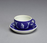 Miniature cup and saucer of white jasper with dark blue jasper dip and white relief decoration, the cup with loop handle, on both are tiny relief scenes including on the cup Hope and Anchor, a female figure next to a tree, possibly the Zodiac Virgo, and two classical figures, and on the saucer a lion and calf, Cupids with a chariot (Bacchanalian scene), two classical figures, Cupids with a goat, a flying Cupid with bow and arrow, and Cupids with an urn.
