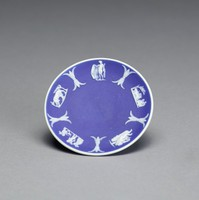 Miniature saucer, or dish, of white jasper with dark blue jasper dip and white relief decoration, the inner rim with a series of tiny relief scenes including flying Cupid with bow and arrow; a group of Cupids at work; Romulus/Remus with a Wolf; a standing figure; Cupids with a chariot (Bacchanalian scene).