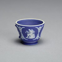 Miniature cup (the handle is missing) of white jasper with dark blue jasper dip and white relief decoration that includes three small relief scenes of a seated figure with scales, a group at an altar, and a seated man with a scythe, with a small floral motif where the handle was.