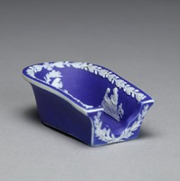 Pipe rest, or sled, of white jasper with dark blue jasper dip and white relief decoration, around the edge is a band of oak leaves with acorns and the interior with three small scenes in white relief including Poor Maria, the Bourbonnais Shepherd, and a mother and child.