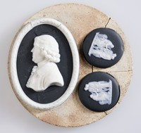 Three black jasper medallions with white relief decoration on fireclay bat, one of Josiah Wedgwood and the other two of classical figures