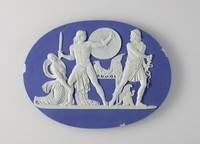 """Oval plaque of white jasper with blue jasper dip on the front and back, on the front with in white relief a variation of """"The Discovery of Achilles"""" featuring a kneeling female, daughter of Lycomedes, grabbing Achilles leg, Achilles with sword and shield, and Menelaus with helmet at his feet, reaching for his sword."""