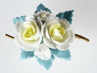 Wedgwood bone china and metal flower brooch with 4 white and yellow flowers above blue leaves.