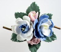 Wedgwood floral brooch with four bone china flowers on green leaves with a metal mount.