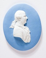 Oval blue jasper medallion with white relief profile portrait of Thomas Bentley (1730-1780) Liverpool merchant and business partner of Josiah Wedgwood in the manufacture and experiment of Ornamental ware.Born at Scropton, Derbyshire. Bentley was introduced to Josiah Wedgwood by Dr. Matthew Turner when Josiah was bedridden in Liverpool in 1762. They seem to have been on terns of friendship from the first. Bentley was, at this time, in partnership with Samuel Boardman of Liverpool, a general merchant, and the firm became Wedgwood's agent.Bentley agreed to become Wedgwood's partner in 1767 for the manufacture of ornamental wares, the partnership deeds being signed in 1769, a few weeks after the opening of the Etruria factory. Bentley settled in London to take charge of the showrooms and decorating studio there, and as a man of widely ranging interests he was able to meet and influence fashionable society to a point where the showrooms became a social centre. Bentley always found difficulty in dealing with subordinates, and staffing troubles were common.Bentley was, however, essential to the design, production and sale of the ornamental wares, and Wedgwood constantly consulted him, and referred to him for approval. In 1772 Bentley married his second wife, Mary Stamford of Derby. He lived at Chelsea from 1769 to 1774. He then removed to the Greek Street showrooms, and from there, in 1777, to Turnham Green, where he remained till his death in 1780.No one ever replaced him as a friend and colleague. A very large number of Wedgwood's surviving letters are addressed to Bentley on business and family problems, but hardly any of Bentley's own letters have survived, so his opinions on the subjects discussed have to be deduced from what Wedgwood has to stay.