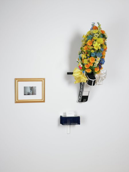 """A multi-part wall mounted sculpture comprising the following three-dimensional elements: a black and white plastic cross bearing the words '16th St Baptist Church' that angles off the wall from a bracket at 45 degrees. The cross is hollow and open at its top end. Emerging from it is a large bouquet of mixed artificial flowers. At opposite sides of the bouquet's base there are two large bows, one yellow, one white. Hung to the left of the cross is a matted photograph in a gold frame. The photographic image is a video still of the cross and flowers described above. Directly below the photograph is a small rectangular wooden shelf bracketed to the wall at a 90 degree angle. The shelf is painted white, trimmed in a navy blue fringe, and topped by a fitted sheet of glass. Atop the shelf is a small white card, folded in half so it stands. The card front is printed with the text, """"As Seen On TV."""""""