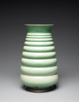 Futura vase consisting of nine stacked convex bands—resembling tires—graduating in size and finished with a wide flared rim. Dark brown glaze at base; emerald green glaze around rim; each band is emerald green at bottom, fading to pale whitish green at top.
