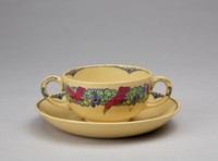 """Small two-handled broth bowl on matching saucer, both of caneware, the outer body of the bowl decorated in the """"Nerots"""" pattern with a band of stylized green flowers and blue berries with six bright red birds resting on it and with three small line-drawn butterflies scattered about, the inner rim with a scalloped edge in blue underglaze enamel with a modified fish scale pattern likewise in blue at the indentations, the two loop handles highlighted in blue underglaze enamel, the round saucer also with a scalloped edge in blue underglaze enamel with a modified fish scale pattern likewise in blue at the indentations."""