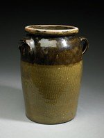 Four-gallon churn with strap-handle on one side, and lug-handle on opposite side, dark greenish-brown glazed body with darker brown band around shoulder.