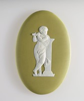 Oval green jasper plaque with white relief figure of a young boy playing the flute