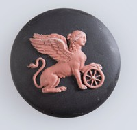Round black jasper cameo with terracotta relief of a winged sphinx with its front left paw resting on a wheel. Because of its effeminate features, we believe this sphinx to be Greek in origin. However winged sphinxs were also common in early Asian and Minoan societies. As yet we do not know the significance of the wheel.