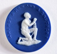 Small oval medallion of dark blue jasperware with white jasper relief of an African slave wearing only a loin cloth, kneeling and in shackles, with his hands grasped together, around him the inscription AM I NOT A MAN AND A BROTHER?