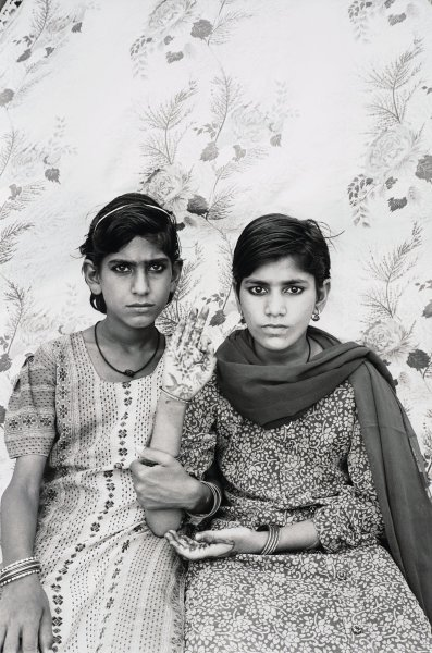 A portrait of two Indian girls who are seated, one raises her hand on which there are henna designs