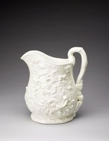 """""""This all-white pitcher is enlived on both sides with relief-molded references to Bacchus. The wine god is portrayed in the guise of a nude child seated amid grape vines and displaying his attributes of a staff and a goblet of wine. These motifs suggest that the pitcher was intended for the dispensing of alcoholic beverages. The assymetrical compostiion of the design and the profusion of ornament – a scrolled medallion embellishing the front and leafage in relief decorating the foot and handle – derive directly from the vocabulary of the Rococo-revival style then at the height of its reign in America."""" From Frelinghuysen, Alice Cooney. American Porcelain, 1770 - 1920. Exh. cat. New York, NY: The Metropolitan Museum of Art, 1989: no. 26, 119."""