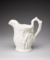 A large mold-formed pitcher decorated with corn stalks and ears throughout. The handle is shaped like a corn stalk.
