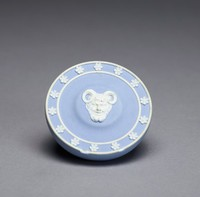 Door knob of solid light blue jasper with white relief decoration, around the edge a border of stylized flowers within two white bands, in the middle of the knob the head of a satyr with horns.