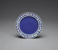 Dish, or stand, of white jasper with dark blue jasper dip and white relief decoration in a pattern of leafy grape vines with bunches of grapes around the rim of the dish.