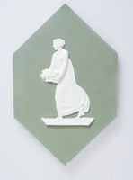 Large hexagonal plaque of white jasper with dark green jasper dip and white relief decoration of a female figure in classical dress holding a basket of flowers, the plaque probably designed for a fireplace surround.
