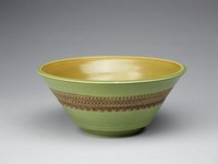 Small footed bowl of white stoneware covered on the outside with a fresh, smooth grass-green glaze and on the inside with a contrasting yellowish-brown glaze that tapers to brown at the well, the outer body decorated around with three bands in a geometric pattern made using the roulette wheel and highlighted in brown glaze.