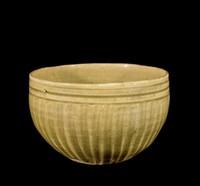 Bowl with carved ribbed sides, slightly concave base, olive-green glaze.