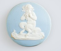 Round blue jasper medallion with white relief of young faun eating grapes, set in metal frame