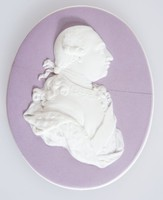 """Oval lilac jasper medallion with white relief profile portrait of George III (1738-1820) was King of Great Britain and Ireland from 25 October 1760 until the union of the two countries on 1 January 1801, after which he was King of the United Kingdom of Great Britain and Ireland until his death. He was concurrently Duke and prince-elector of Brunswick-Lüneburg (""""Hanover"""") in the Holy Roman Empire until his promotion to King of Hanover on 12 October 1814. He was the third British monarch of the House of Hanover, but unlike his two predecessors, he was born in Britain, spoke English as his first language, and never visited Hanover. Modelled with slight alterations from a wax portrait by Isaac Gosset in about 1775."""